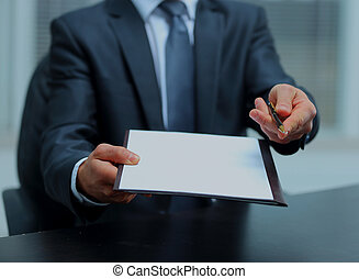Businessman giving pen for your signature on clipboard.