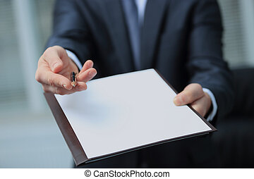 Businessman giving pen for your signature on clipboard