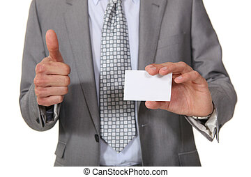 Businessman giving the thumbs up as her displays business card