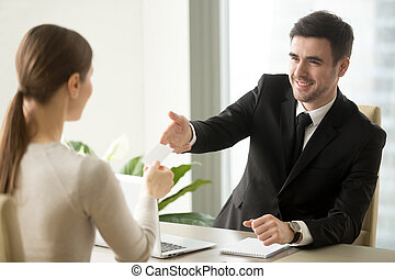 Businessman giving visiting business card to businesswoman at of
