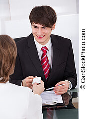 Businessman Giving Visiting Card To Colleague At Desk