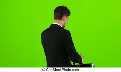 Businessman goes to work, with a diplomat he waves his hand to others. Green screen