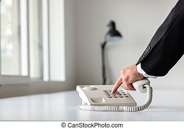 Businessman hand dialing a telephone number using white...