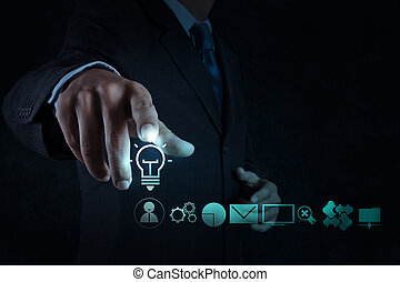 businessman hand draws lightbulb with new computer interface as solution business concept