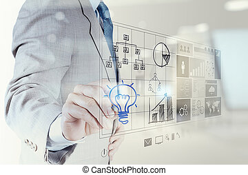 businessman hand draws lightbulb with new computer interface