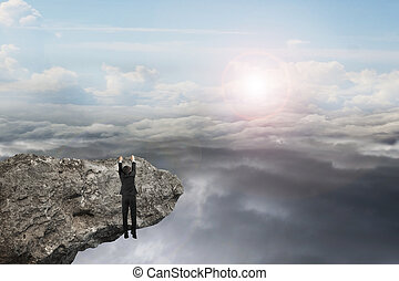 businessman hand hanging on cliff with natural sky daylight cloudscape background