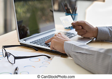 Businessman hand holding a Credit card intent to made a online payment with his computer laptop on his desk.