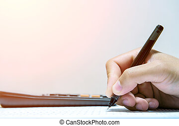 Businessman hand holding a pen working on document.