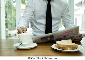 Businessman hand holding coffee cup  and reading newspaper with slice of toast