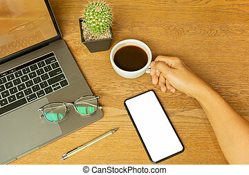 Businessman hand holding coffee cup with laptop and eyeglasson wooden desk.