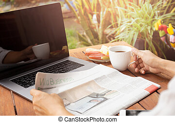 Businessman hand holding coffee reading newspaper with laptop on table.