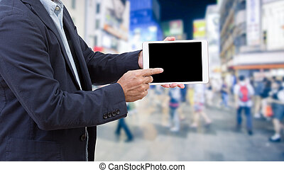 Businessman hand holding tablet computer with blurred image of crowd