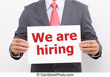 Businessman hand holding We are hiring board. wearing suit and red necktie