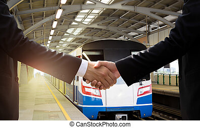 Businessman hand shake agreement with public transport sky train in background.