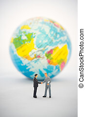 Businessman hand shaking in front of  the global.