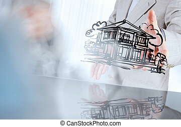 businessman hand showing a house on touch screen coumputer as co