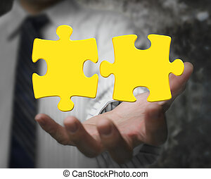 Businessman hand showing two 3D gold jigsaw puzzle pieces