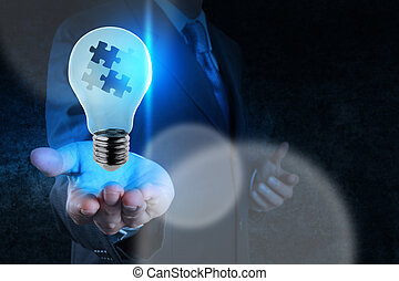 businessman hand shows light and puzzle partnership