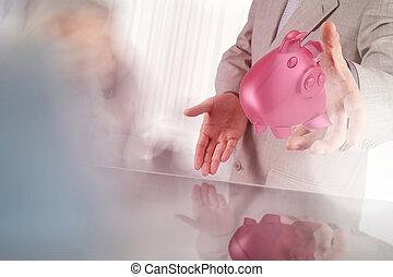 businessman hand shows piggy bank as concept