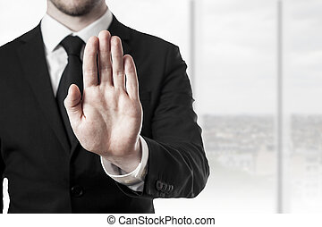 businessman in black suit holding hand stop in office room