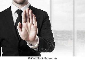 businessman hand stop - businessman in black suit holding...