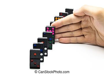 Businessman hand stopping domino effect