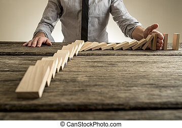 Businessman hand stopping domino effect. Rough wooden table...