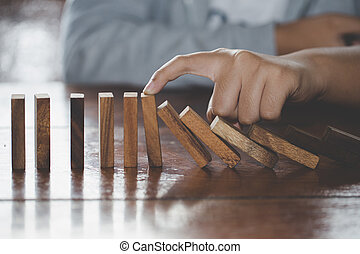 Businessman hand stopping falling wooden dominoes effect from continuous toppled or risk, strategy and successful intervention concept for business, game strategy, Invesment and Risk Management.