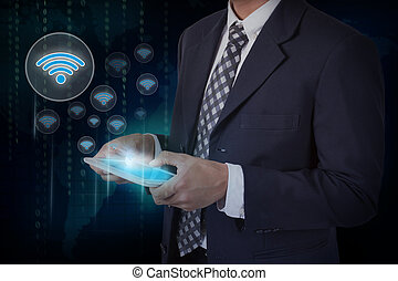 Businessman hand touch screen wifi symbol on a tablet.