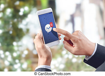 businessman hand touch social media icon on mobile screen