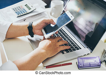 businessman hand using smart phone and keying the data to laptop