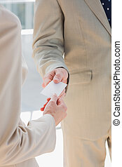 Businessman handing card to businesswoman