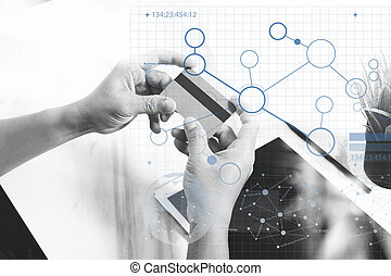 Businessman hands holding plastic credit card and using digital tablet and laptop computer. Online shopping concept. On marble table, Sun flare effect