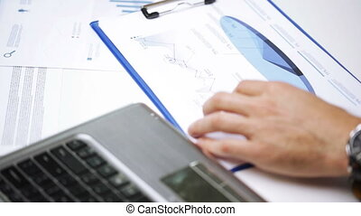 businessman hands with laptop and papers in office