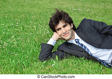 businessman has rest, lying on grass