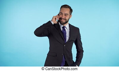 Businessman have conversation using mobile phone isolated on blue background. Business guy in formal suit gladly talks with colleague. Office employee, wage worker, weekdays concept