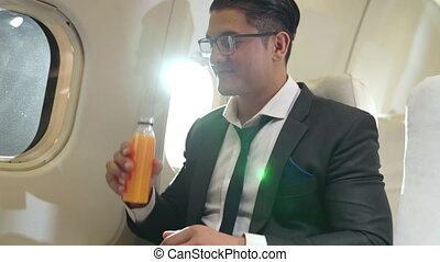 Businessman have orange juice served by an air hostess in ...