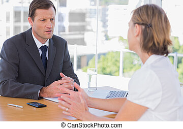 Businessman having a discussion with a job applicant in his...