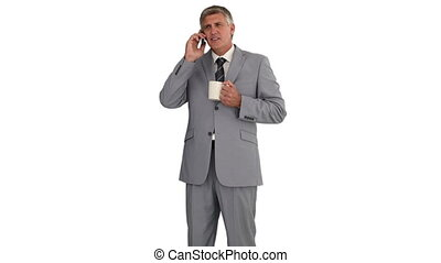 Businessman having a phone call while he is holding a cup of tea isolated on a whitebackground