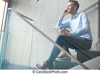 Businessman having break on the steps