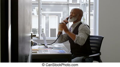 Businessman having coffee while talking on landline and using laptop at desk 4k