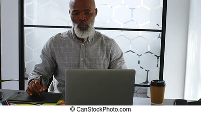 Businessman having coffee while using graphic tablet on desk 4k