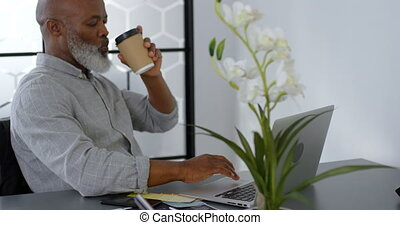 Businessman having coffee while using laptop on desk 4k