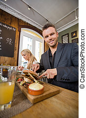 Businessman Having Food With Colleague In Coffeeshop