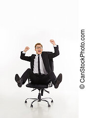 Businessman having fun. Cheerful young businessman sitting on the office chair with his arms raised while isolated on white
