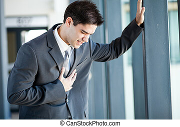 businessman having heart attack - young businessman having...