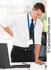 businessman having lower back pain in office