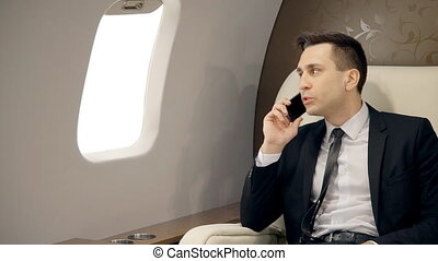 Businessman having mobile phone conversation in luxury private aircraft.