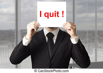 businessman hiding face behind sign i quit - businessman in...