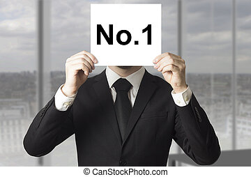 businessman hiding face behind sign number one